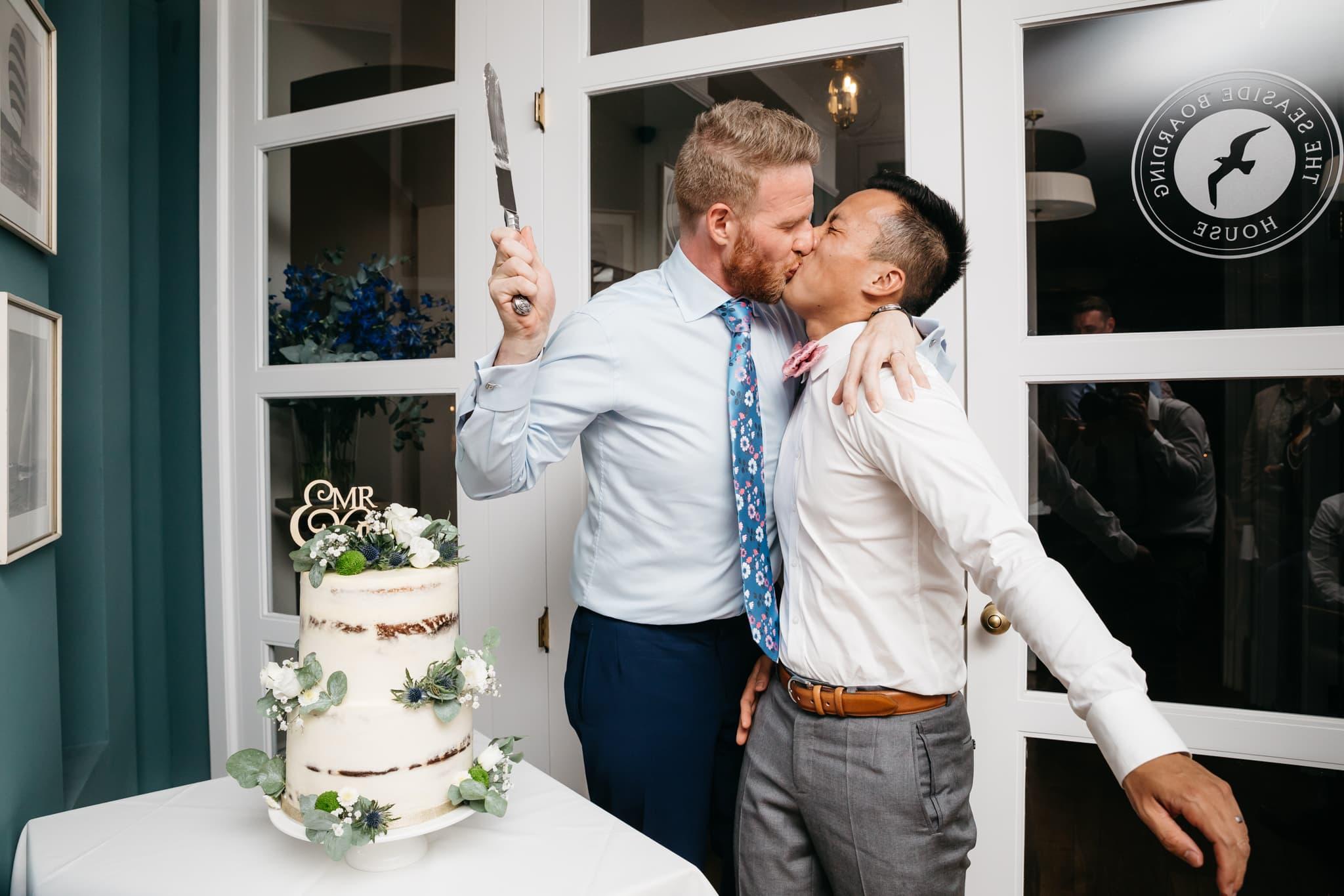 Same sex couple cutting their wedding cake