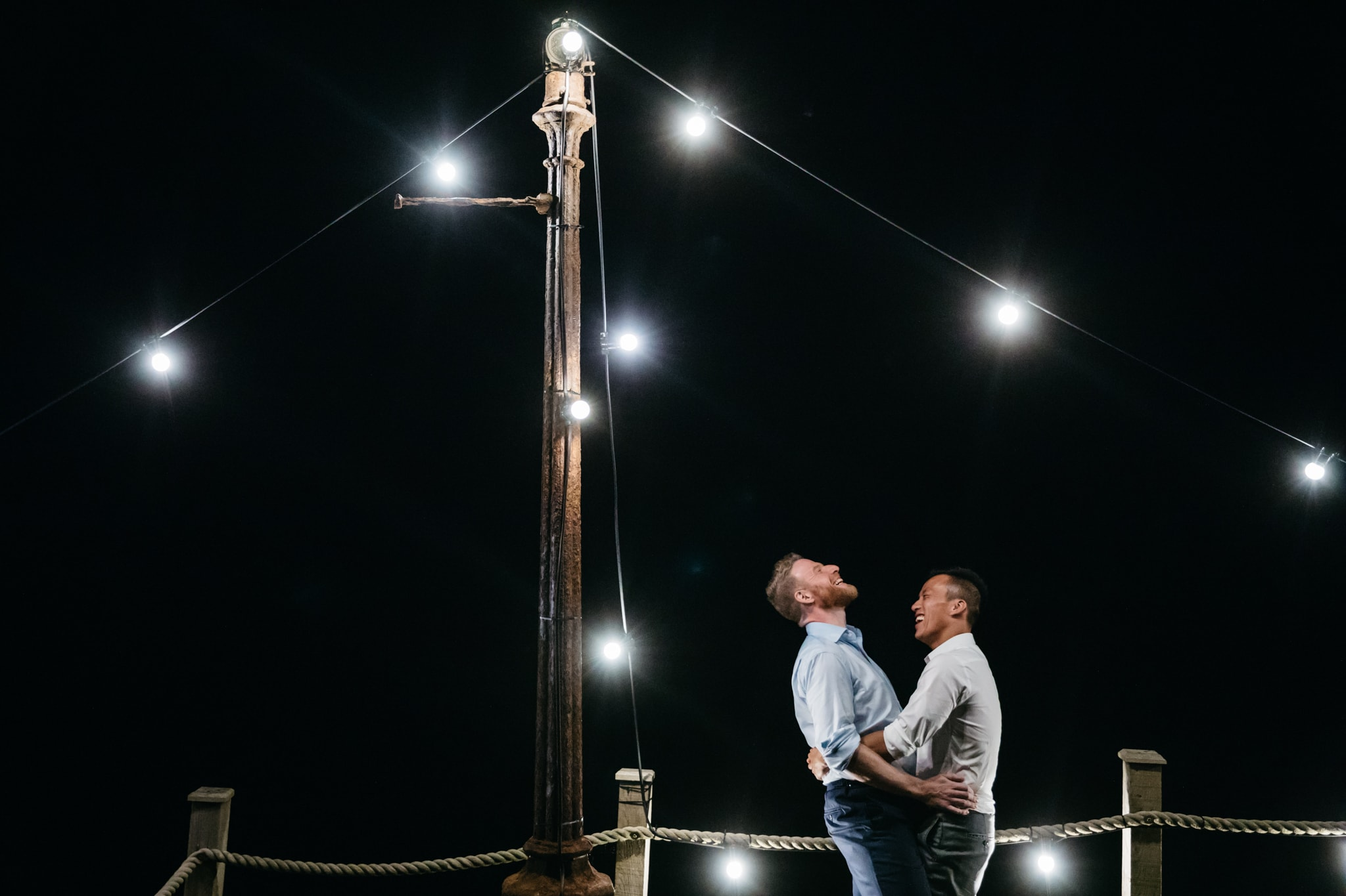 Same sex couple at the end of their wedding under festoon lighting