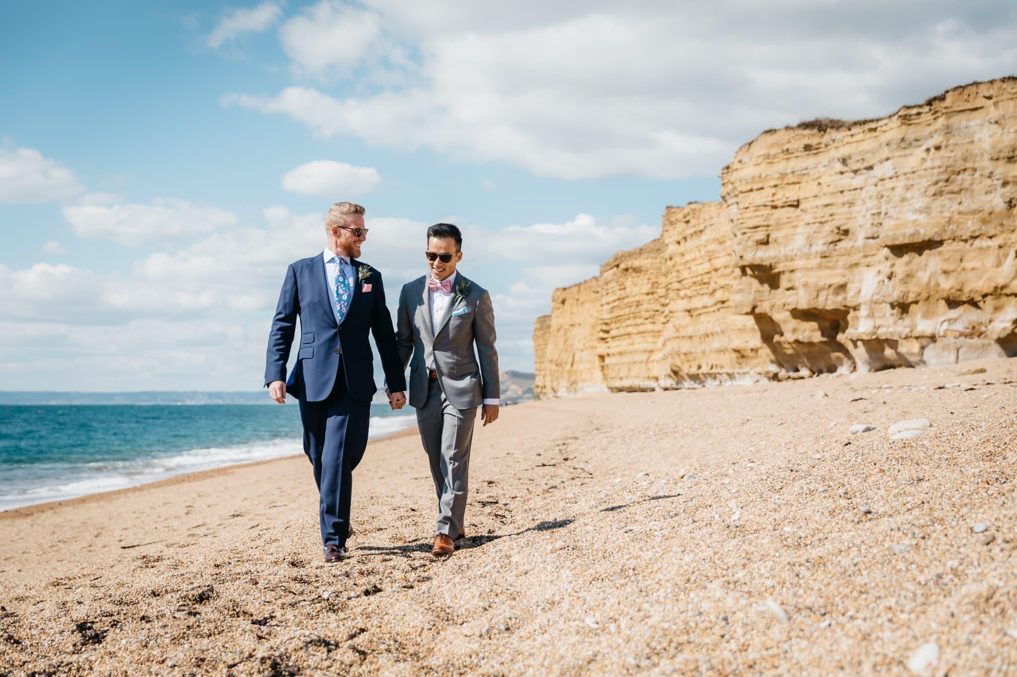 Same sex couple walking along the beach to their wedding